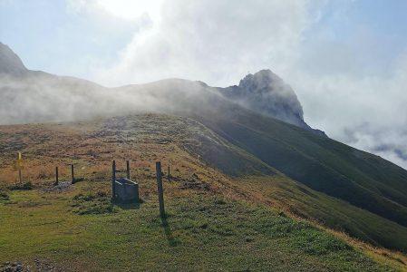 Gipfelkreuz hinter den Wolken am Kaiserjochhaus
